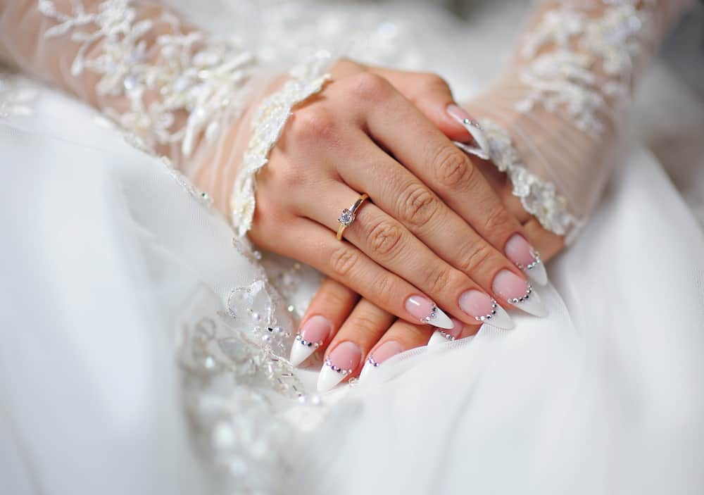 hands of a bride with an engagement ring and a wedding manicure